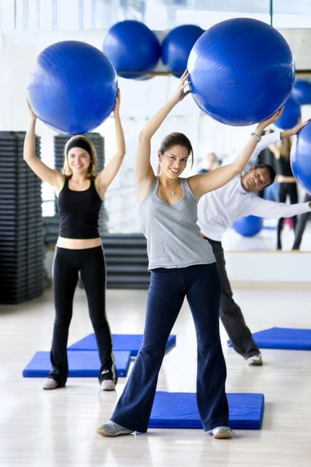 People in aerobics class at the gym with pilates ball