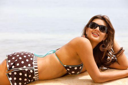 Beautiful woman in bikini lying on the beach