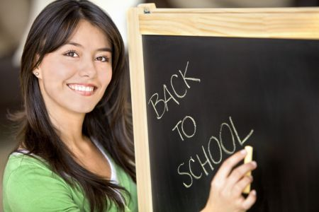 Beautiful woman writing 'Back to school' in a blackboard