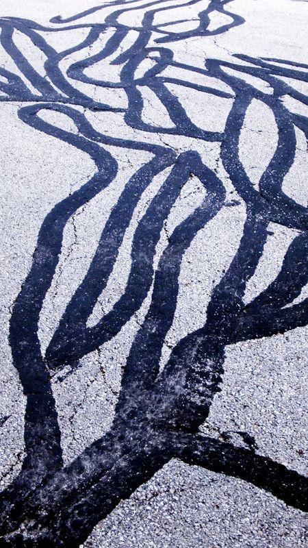 Street grunge: maze of sealant on cracked asphalt