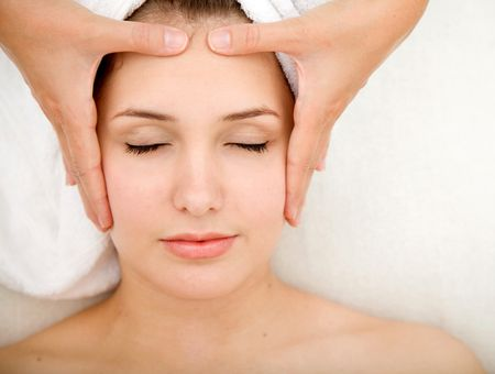 Woman at a spa getting massage on her face