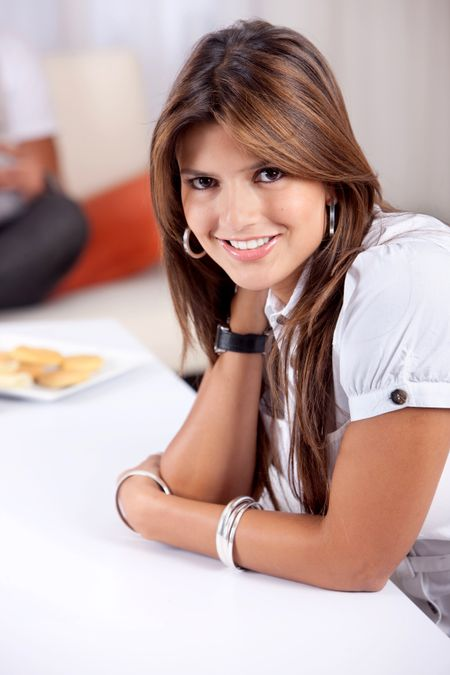 Woman portrait smiling leaning on a table indoors