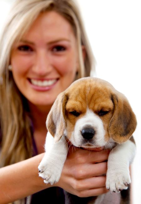 Beautiful woman smiling holding a puppy isolated