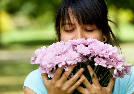 Woman smelling a bouquet of flowers outdoors