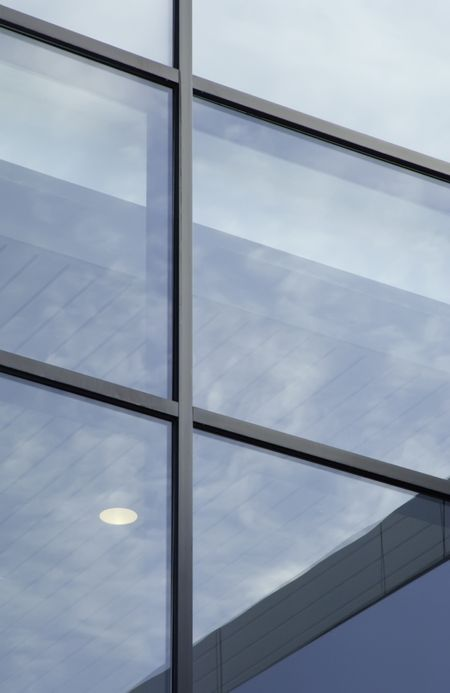 Reality indoors and out: windows of campus building reveal ceiling and light fixture while reflecting the sky