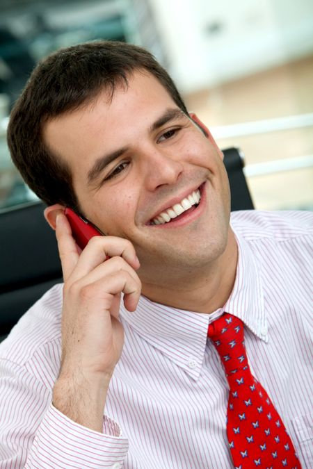 business man smiling and talking on a mobile phone in an office