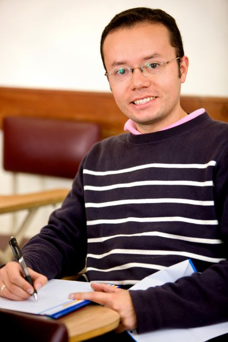 Male student with a notebook smiling indoors