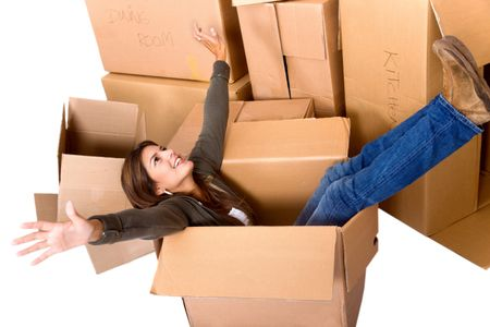 pretty woman sitting inside a box among a stack of moving boxes