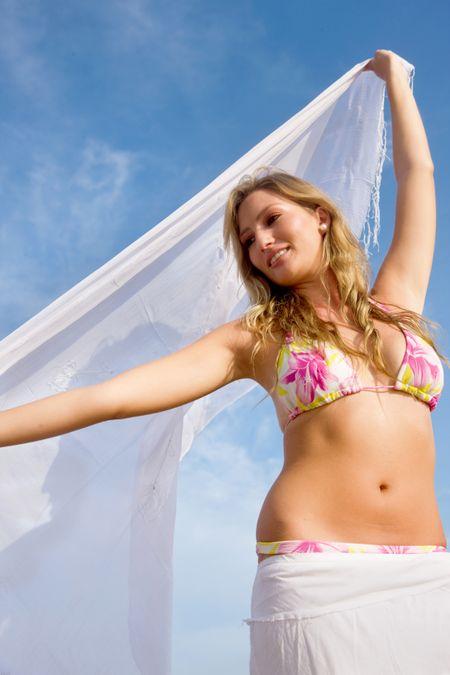 Beautiful girl having fun at the beach waving a white sarong