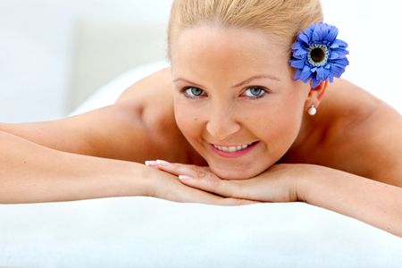 Woman with a flower on her head relaxing at a spa