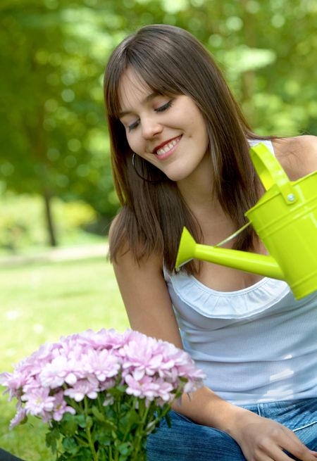 Beautiful happy girl watering a plant outdoors