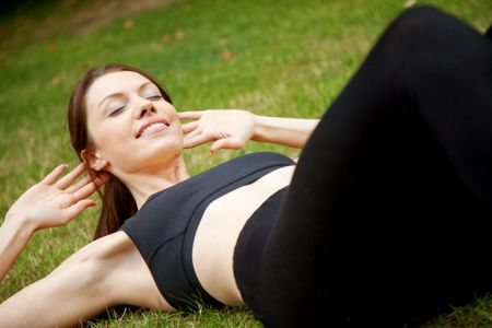 Beautiful happy woman doing exercise for her abs outside