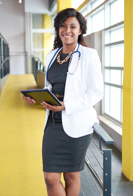 Portrait of a female doctor holding her patient chart on digital tablet in bright modern hospital