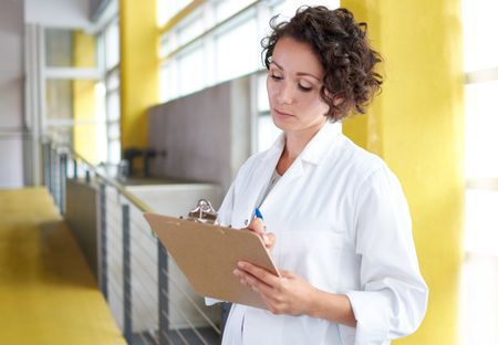 Portrait of a female doctor holding her patient chart in bright modern hospital