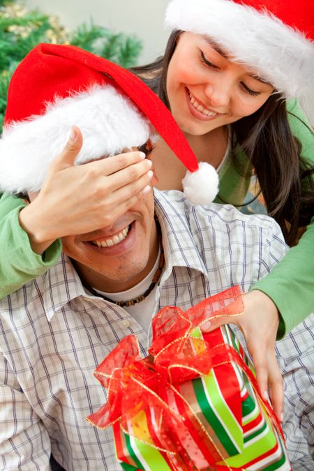 Woman giving a surprise Christmas gift to a man
