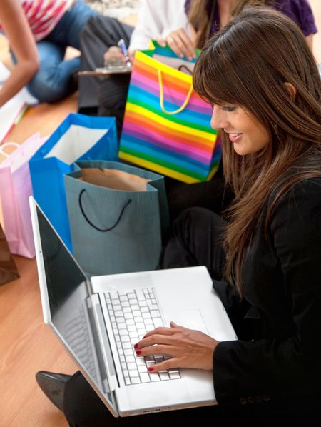 Woman with a computer and bags shopping online