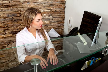 Female receptionist working on the computer at the office