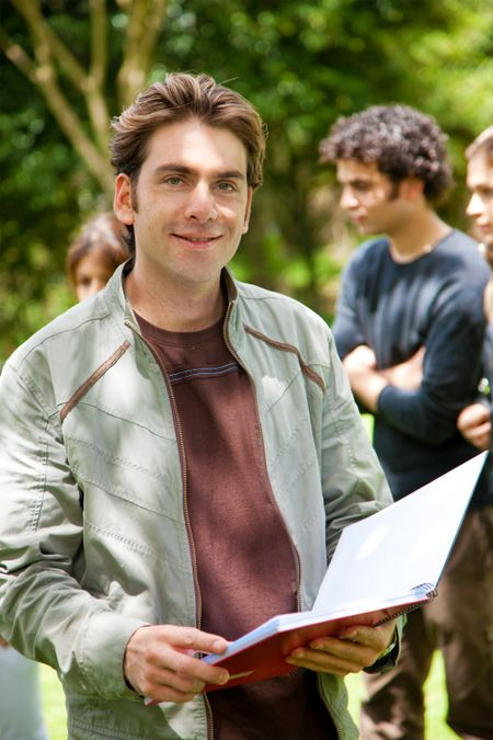 Handsome male student holding a notebook outdoors