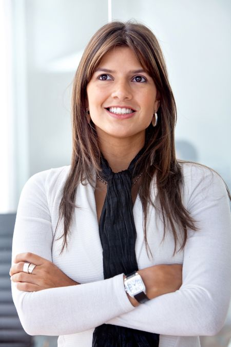 Confident business woman smiling and looking up in her office