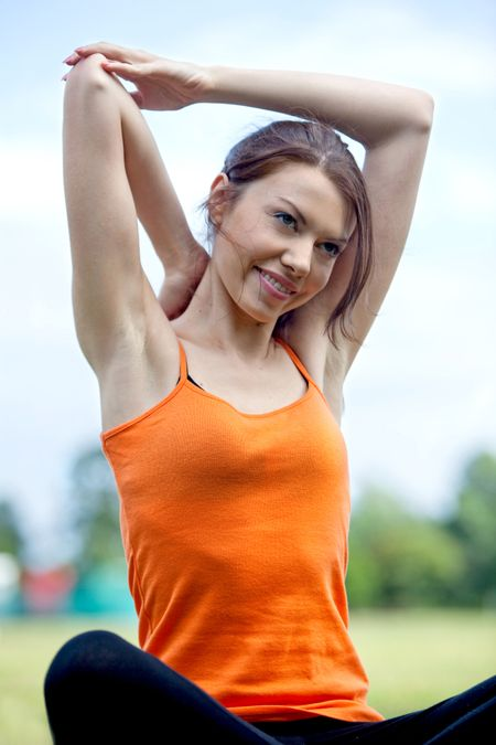 Woman doing stretching exercise for her arms outdoors