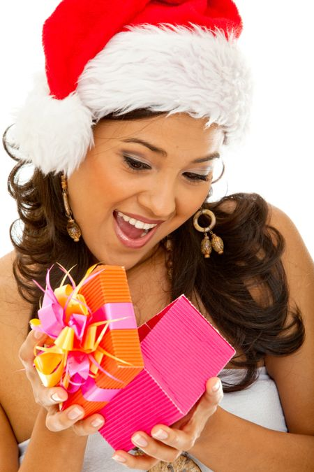 Christmas woman wearing a santa hat opening a gift isolated on white