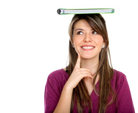 Thoughtful female student with a notebook on top of her head isolated on white
