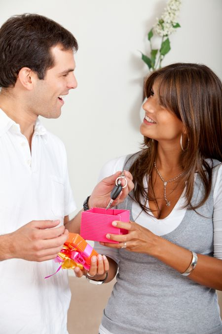 Loving woman giving a gift to a man and smiling