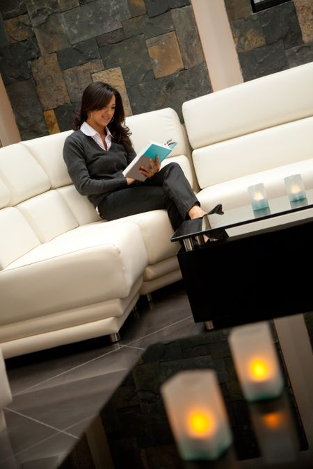 Business woman reading a book at the lounge of a hotel