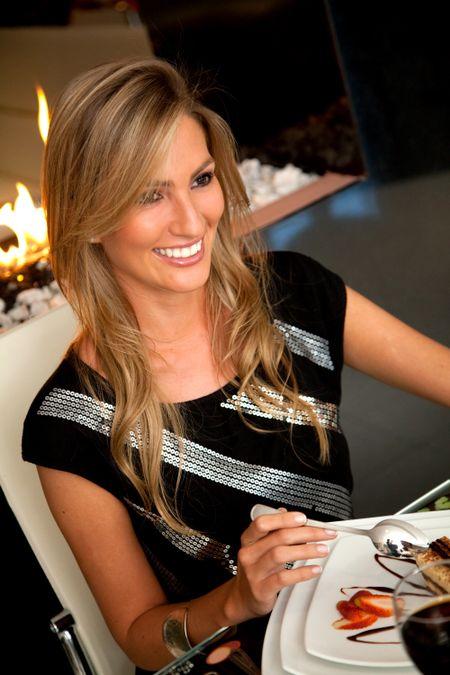 Beautiful woman eating dessert at a romantic dinner