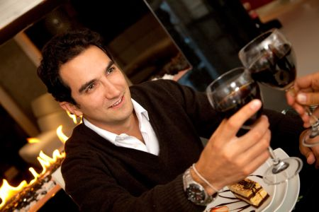 Man at a romantic dinner toasting with wine