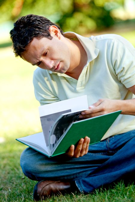 Young male student reading a book outdoors