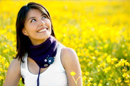 Pensive woman sitting on a beautiful meadow