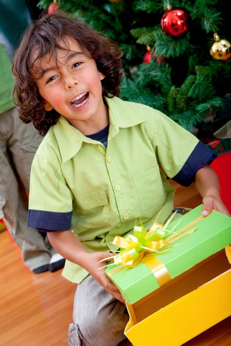Happy kid opening a Christmas gift and smiling