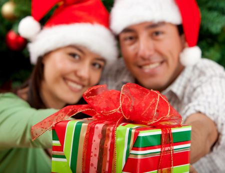 Christmas couple smiling next to a tree with a present