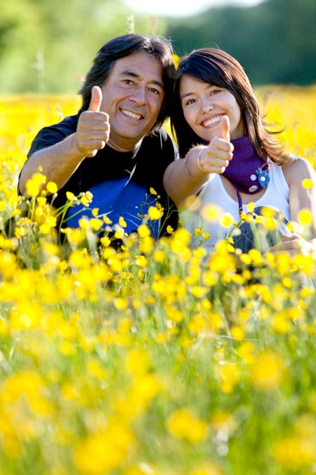 Father and daughter with thumbs up at a meadow