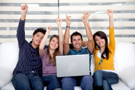 Excited group of people sitting on the sofa with a laptop