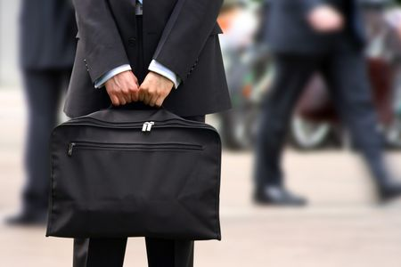 business man holding a briefcase in a fast moving corporate environment