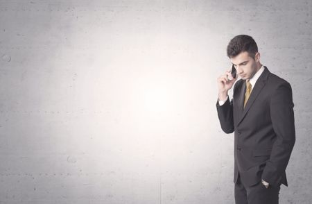 Young sales business person in elegant suit standing in front of clear empty grey wall background while talking on the phone