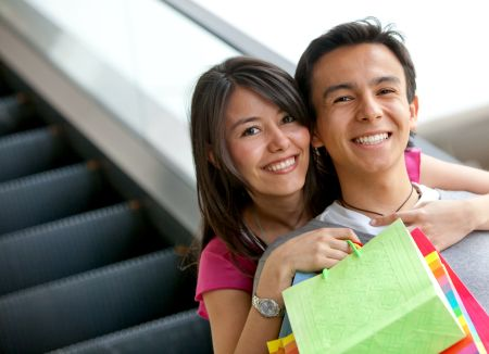Happy couple at a shopping center with bags