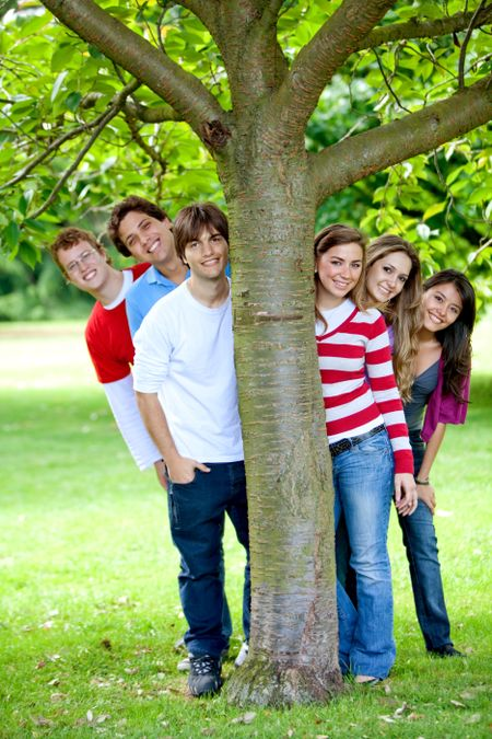 Happy friends at the park hiding behind a tree
