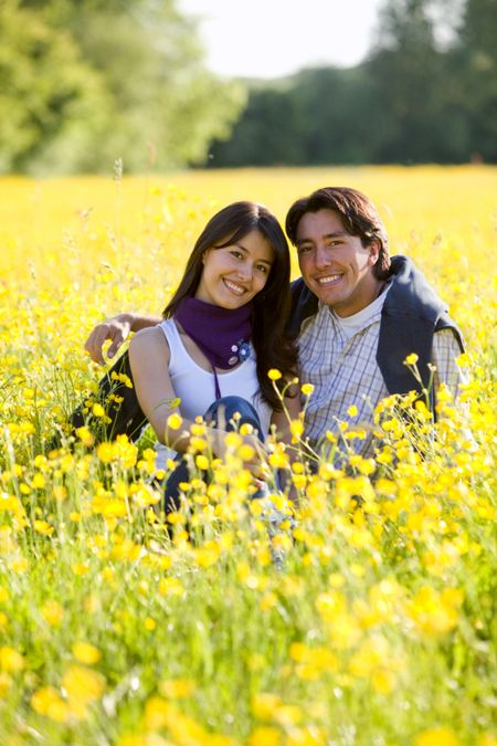 Beautiful couple outdoors in a meadow smiling