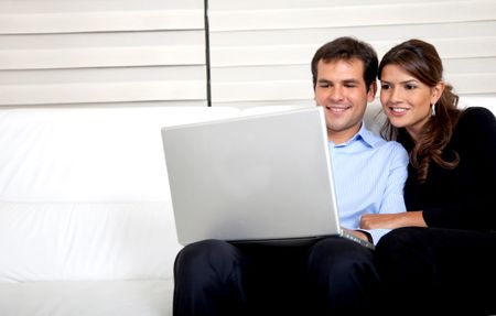 Couple at home working on a laptop