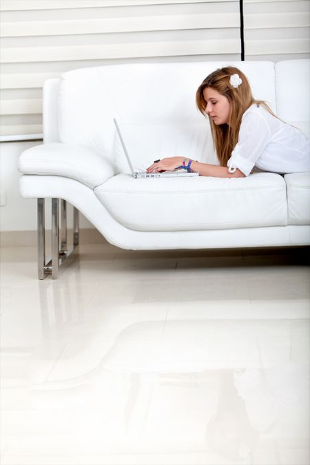 Girl lying on a sofa with a laptop