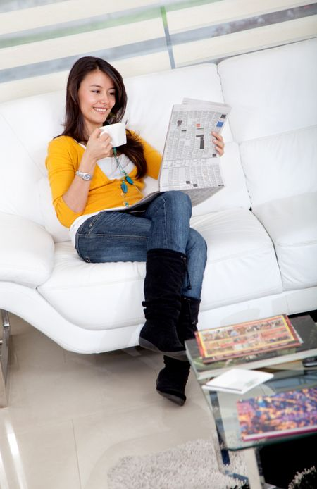 Woman reading the newspaper and drinking coffee at home