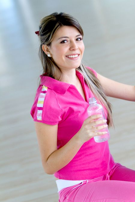 Beautiful woman portrait at the gym holding a water bottle