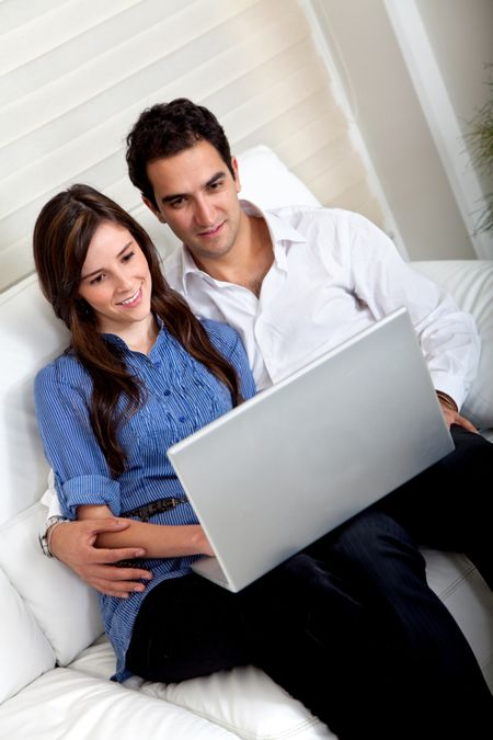 Beautiful couple with a laptop sitting on a coach indoors
