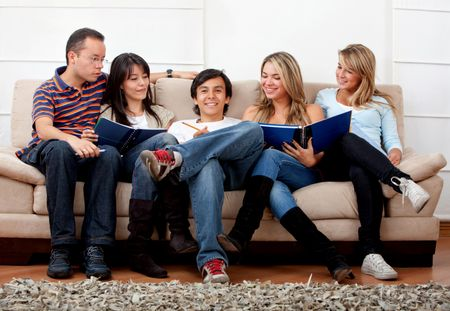 Happy group of students sitting on a couch studying indoors