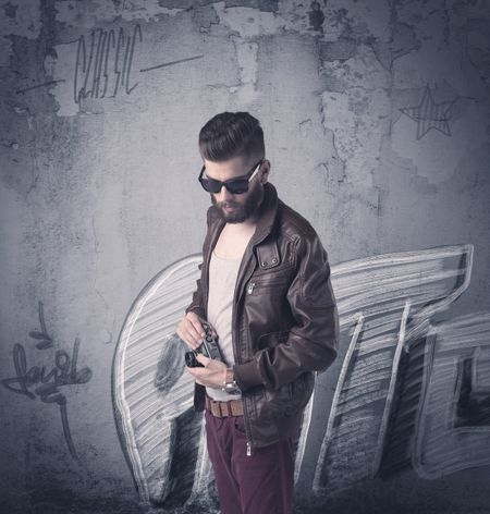 A handsome hipster guy with beard and sunglasses standing in front of an urban wall with graffiti concept