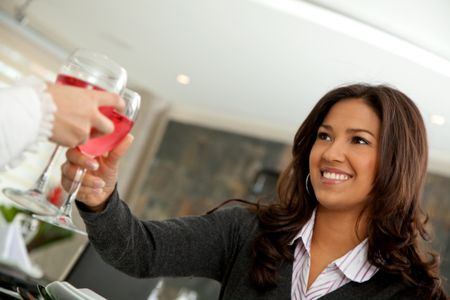 Beautiful woman toasting at a restaurant looking happy