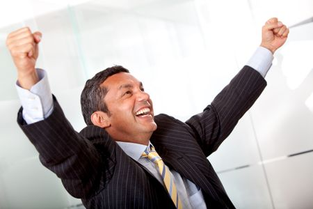 business man standing with his arms up representing his success isolated over a white background